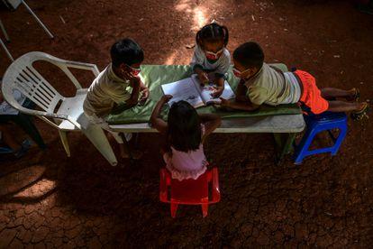 Un grupo de niños indígenas emberá consulta un libro durante una clase, en marzo de 2021, en Puru Embera, provincia de Colon, Panamá. En tiempos de pandemia y sin conexión a internet, estudiantes como ellos reciben lecciones gracias a profesores que se desplazan largas distancias hasta sus comunidades.