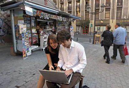 Una pareja se conecta a internet desde un ordenador portátil a través de wifi