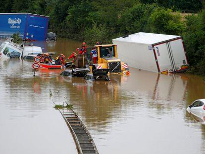 Miembros de un equipo de rescate trabajan junto a coches atascados en la carretera tras las fuertes lluvias en Erftstadt, Alemania.