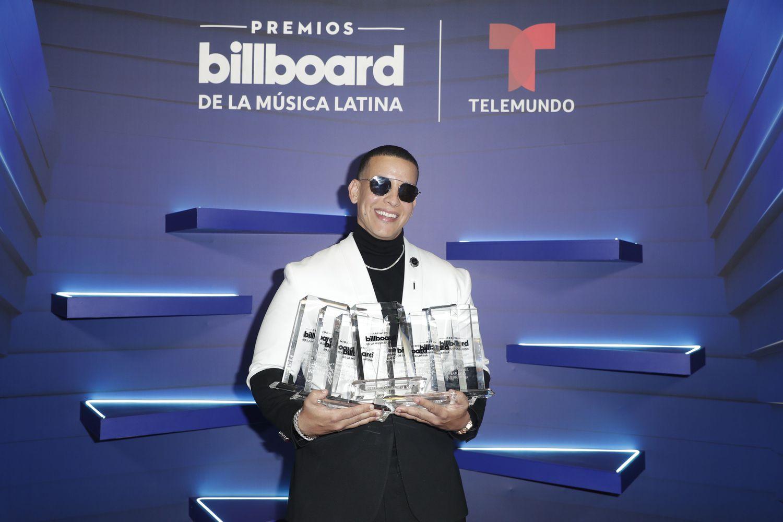 El cantante puertorriqueño Daddy Yankee mientras posa con sus siete Premios Billboard.