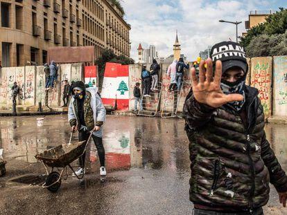 Varios manifestantes intentan traspasar el 11 de febrero los muros de hormigón levantados para impedir el acceso de civiles al Parlamento libanés en Beirut.