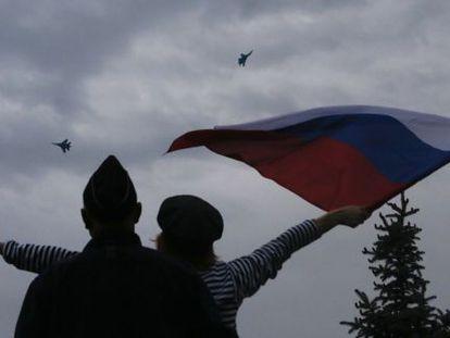 Una mujer ondea una bandera rusa en Sebastopol ante la presencia de aviones rusos en la celebración del Día de la Victoria.