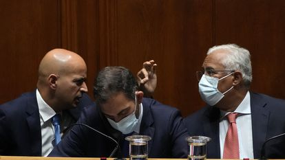 Finance Minister Joao Leao, left, talks to Prime Minister Antonio Costa during a debate at the Portuguese Parliament before the voting of the government's state budget, in Lisbon, Wednesday, Oct. 27, 2021. In the center is Secretary of State for Parliamentary Affairs Duarte Cordeiro. Portuguese President Marcelo Rebelo de Sousa, who has no governing powers but oversees the smooth running of the country, has warned that if parliament does not approve the budget he will call a snap election. (AP Photo/Armando Franca)