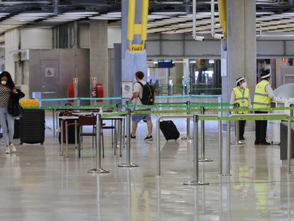 Pasajeros procedentes de Londres caminan entre los pasillos delimitados el 24 de junio de 2020.