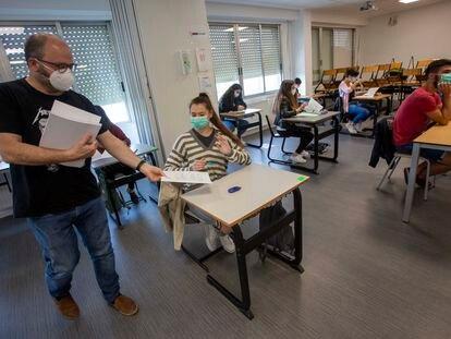 Un profesor reparte exámenes en el colegio Axular de San Sebastián.
