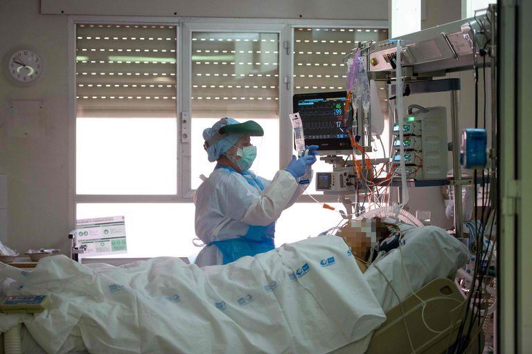 Un trabajador sanitario atiende a un paciente de coronavirus en una Unidad de Cuidados Intensivos del hospital Príncipe de Asturias de Alcalá de Henares (Madrid).