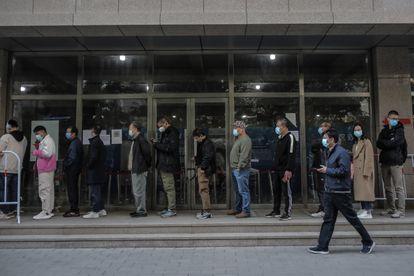 Ciudadanos chinos hacen cola en Pekín para recibir una dosis de la vacuna contra el coronavirus, este sábado.
