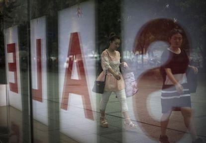 Dos mujeres, reflejadas ante unos almacenes en rebajas, en Pekín