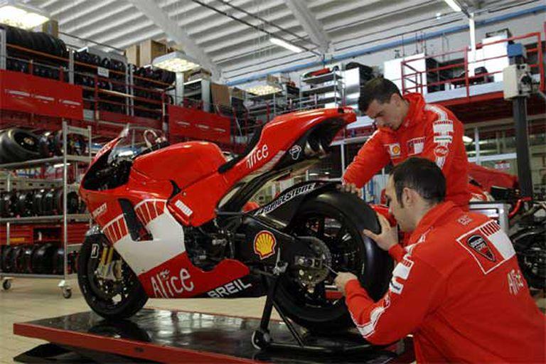 Dos operarios de Ducati ajustan una moto.