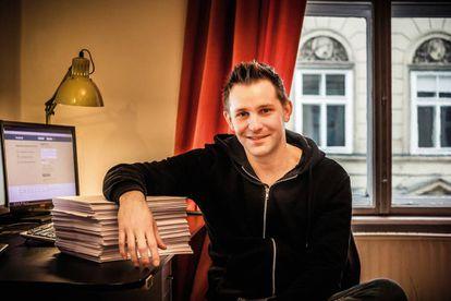 Max Schrems, en su apartamento de Viena, apoyado sobre las 1.200 hojas de información personal que Facebook recopiló sobre él.