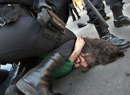 Los <i>mossos</i> reducen a un joven durante los incidentes registrados ayer en la Gran Vía de Barcelona.
