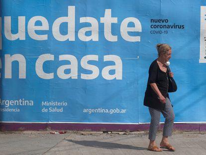 Una mujer pasa frente a un cartel gubernamental que pide a la población que se quede en casa
