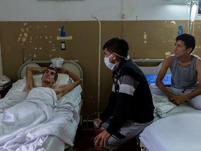 Lucas, de 24 años y recuperado tras haber sufrido tuberculosis, visita a los pacientes Jorge (izquierda), de 40 años, y Arturo Maldonado, de 25, hospitalizados por padecer esta enfermedad infecciosa en el hospital público de Muniz en Buenos Aires, Argentina, el 25 de enero de 2019. Magali Druscovich/ REUTERS