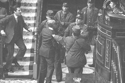 Varios guardias civiles zarandean al general Manuel Gutiérrez Mellado, vicepresidente del Gobierno, mientras el presidente Adolfo Suárez (a la izquierda) acude en su auxilio.