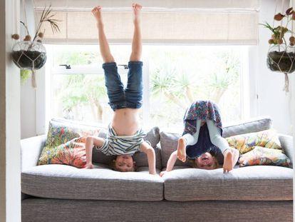 Dos niños juegan en el sillón de su casa.