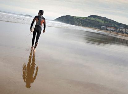Un surfista en la playa de Zarautz, en cuyo extremo occidental parte el paseo costero que lleva, en algo más de tres kilómetros, a Getaria.