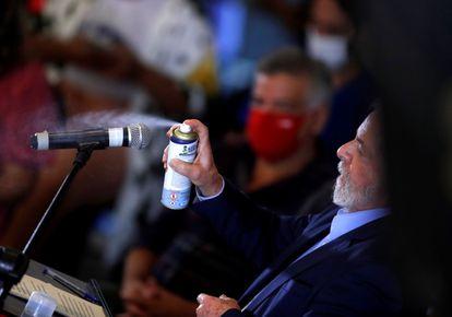 Lula da Silva rocía desinfectante al micrófono durante la rueda de prensa.