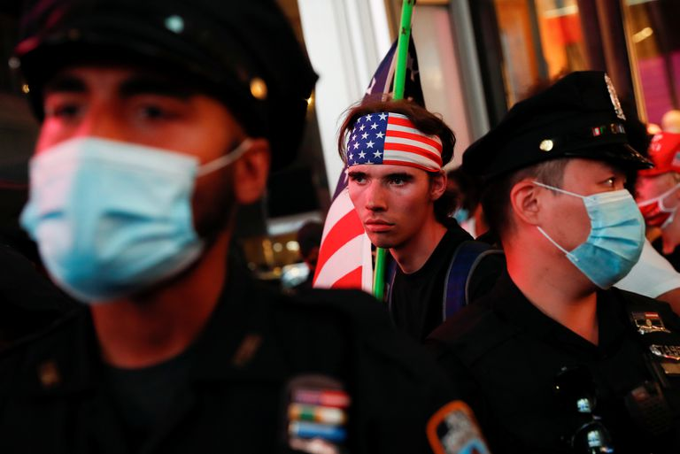 A supporter of Donald Trump holds up the American flag during a demonstration in Times Square, New York.