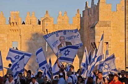 Israelíes ondean banderas fuera de la Puerta de Damasco en la Ciudad Vieja de Jerusalén, el 15 de junio de 2021, celebrando el aniversario de la ocupación israelí de 1967 de Jerusalén Este.