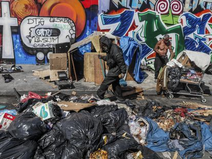 Dos hombres rebuscan entre la basura en una calle de Los Ángeles.