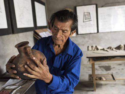 Enrique Niquín observa una vasija de su museo.