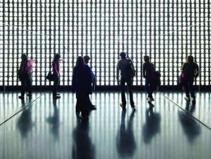Varios visitantes observan la obra de Alfredo Jaar.