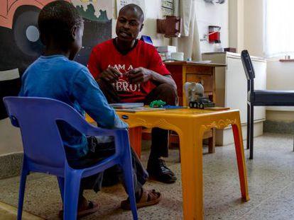 Lewis, de ocho y portador de VIH, asiste a su primera sesión de apoyo psicológico con el terapeuta Momo Aggrey, de Médicos sin Fronteras.