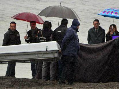 El momento del levantamiento de un cadáver en la playa del Tarajal tras la tragedia.