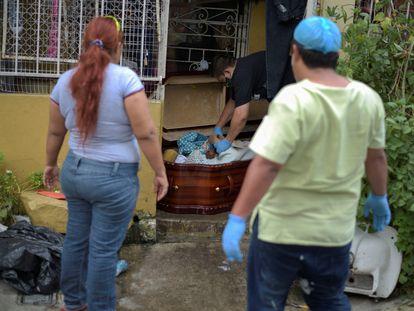 Una mujer observa un ataúd con el cadáver de su madre, fallecida por coronavirus. En el video, habitantes de Guayaquil muestran los cadáveres de sus familiares dentro de las casas.
