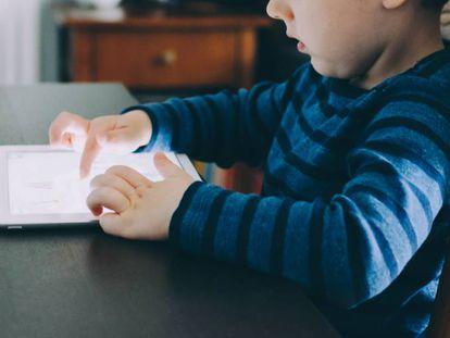 Un niño mira con atención su tableta.
