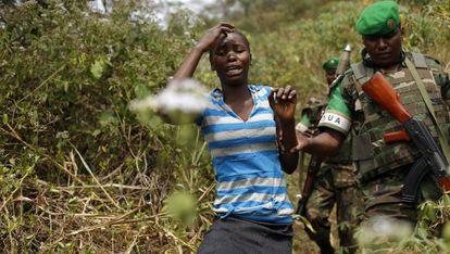 Un militar ruandés escolta a una mujer en las afueras de Bangui.