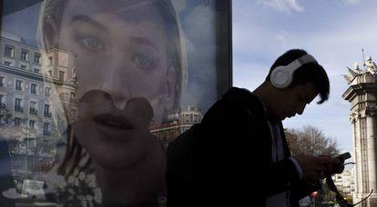Un joven consulta su móvil junto a la Puerta de Alcalá, en Madrid.