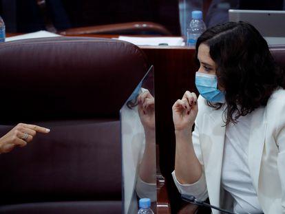 Isabel Díaz Ayuso habla con una diputada regional, en la Asamblea de Madrid este jueves.