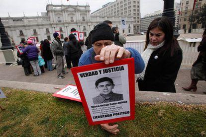 Un activista de los derechos humanos coloca un cartel con la foto de uno de los desaparecidos durante la dictadura de Pinochet frente al palacio presidencial.
