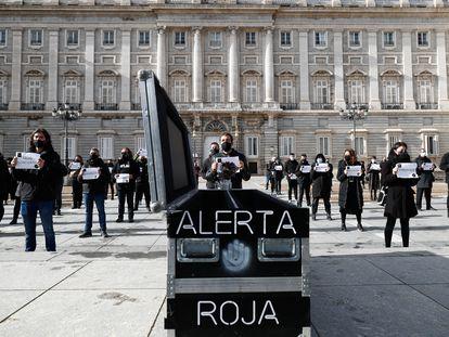 """Convocados por el movimiento Alerta Roja, varias trabajadores de espectáculos y  eventos realizan performance y portan pancartas frente al Palacio de Oriente para protestar por """"la agonía que padece"""" su sector debido al covid en Madrid."""