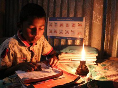 Un niño hace sus tareas escolares en su casa, bajo la luz de una vela, en una aldea de Bangladés.