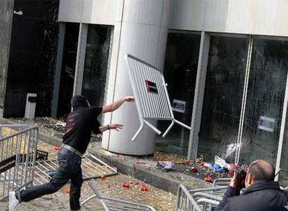 Un manifestante contra los despidos de Nissan tira una valla contra la sede en Barcelona.
