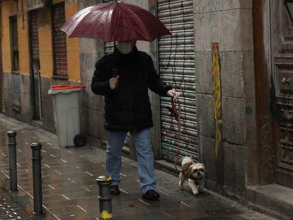 Un hombre pasea a su perro en el madrileño barrio de Malasaña.