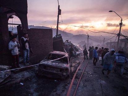 El puerto chileno de Valparaíso, a 120 kilómetros de Santiago y compuesto por 42 cerros, se enfrenta de nuevo a una tragedia a causa de las llamas. En la imagen, un grupo de vecinos observan el estado de las viviendas.