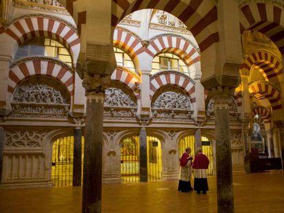Dos sacerdotes conversan entre los arcos de la Mezquita de Córdoba.