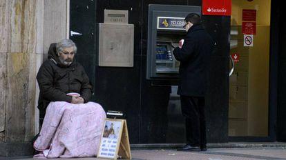Un mendigo junto a un cajero en Madrid, en 2013.