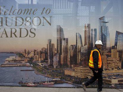 Un trabajador de la construcción pasa por delante de un cartel promocional del nuevo barrio neoyorkino de Hudson Yards. |