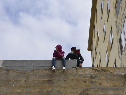 Dos niños sentados sobre un muro en la nave de primera acogida del polígono del Tarajal, a 20 de mayo de 2021, en Ceuta (España). Durante los últimos tres días Ceuta ha recibido 8.000 ciudadanos marroquíes, de los cuales 5.600 ya han sido expulsados o retornados voluntariamente al Reino alauita.