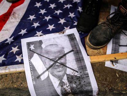 Palestinos pisan banderas estadounidenses y una foto del presidente de Ee UU, Donald Trump, durante una protesta en el norte de la Franja de Gaza (Palestina) el 7 de diciembre de 2017.