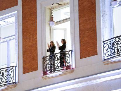 Díaz Ayuso (derecha) se sumó al homenaje a los sanitarios aplaudiendo desde el balcón de la Real Casa de Correos.
