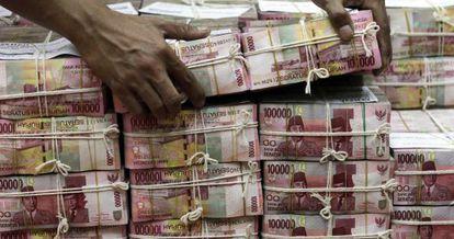 Un hombre mueve paquetes de billetes de 100.000 rupias.