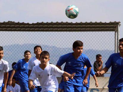 Alumnos de la escuela de 'LaLiga, Valores y Oportunidad' pugnan por un balón durante un entrenamiento.