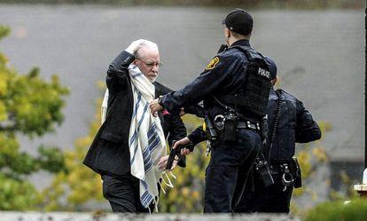 Un hombre habla con la policía tras salir de la sinagoga del tiroteo.