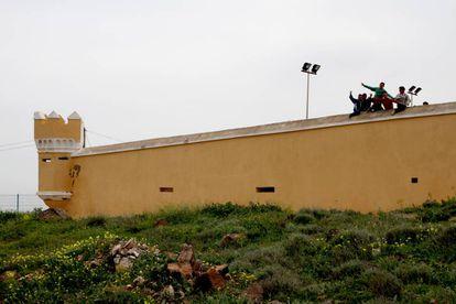 Un grupo de niños saluda desde el centro de menores de La Purísima, en Melilla, un antiguo fuerte militar.
