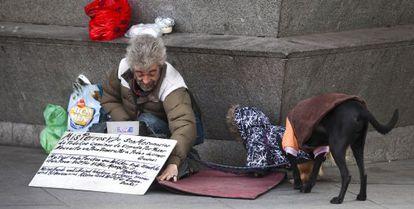 Un indigente, con dos perros, mendigando en una calle de Madrid.